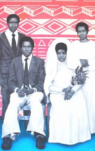 A portrait of a married couple sitting in the foreground wearing their wedding attire, with two other persons standing behind them. The floor is a bright blue and the background is pink with white geometric shapes running horizontally across the image.